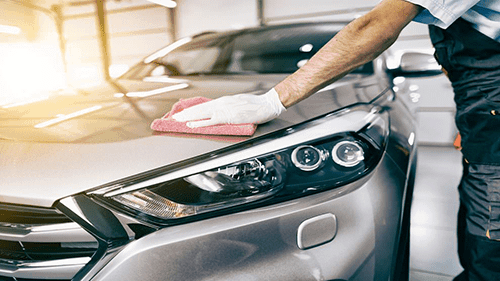 man waxing car