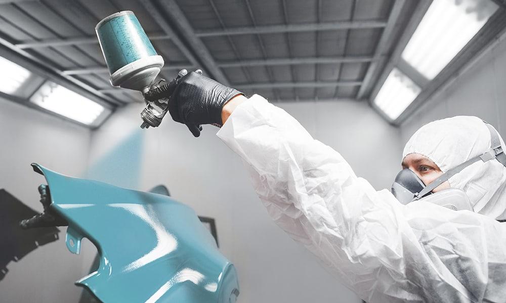 man painting car fender